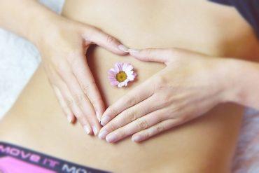 Une fleur posée sur l'abdomen d'une femme